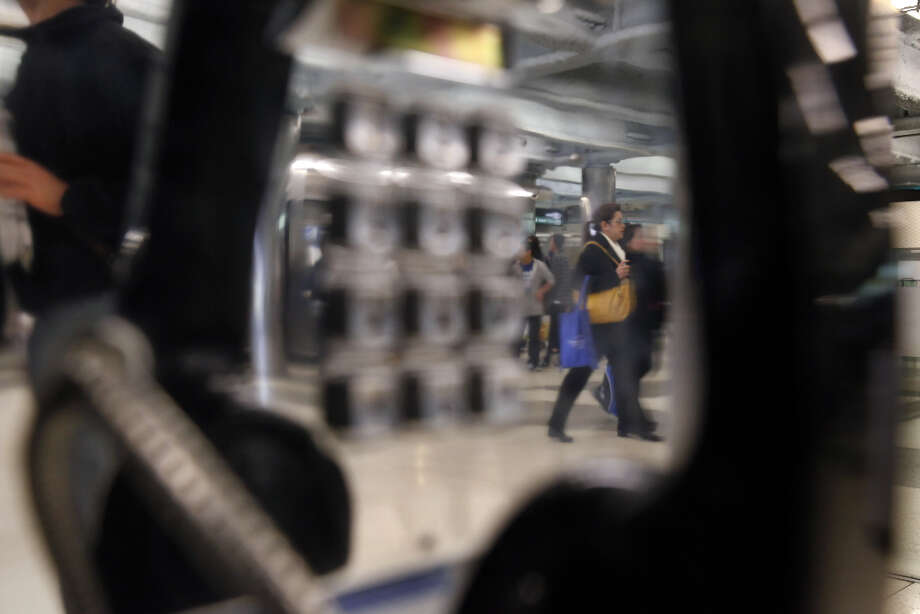 BART patrons walks past pay phones at the Powell Street BART station in San Francisco, Calif. Photo: Carlos Avila Gonzalez, The Chronicle / ONLINE_YES