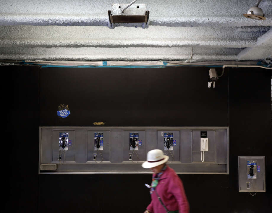 A BART patron walks past a row of pay phones at the Powell Street BART station in San Francisco, Calif. Photo: Carlos Avila Gonzalez, The Chronicle / ONLINE_YES