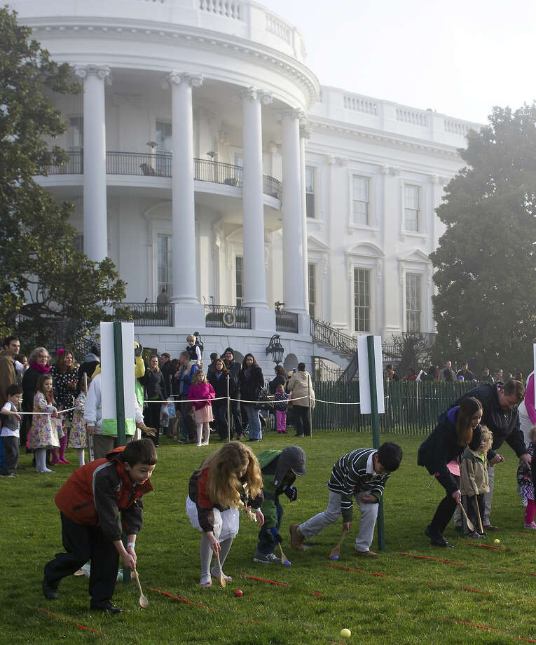 Children race to roll eggs as they participate in the White House Easter Egg Roll on the South Lawn of the White House in Washington, DC, April 1, 2013. US President Barack Obama hosts the annual event, featuring live music, sports courts, cooking stations, storytelling and Easter egg rolling. Photo: SAUL LOEB, AFP/Getty Images / 2013 AFP