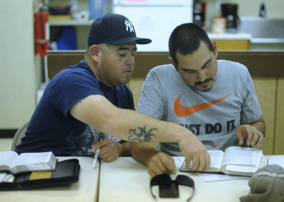 Adam Garcia (left) who works laying pipe in the Eagle Ford Shale energy sector, assists Juan Rodriguez with a Bible passage during a meeting at Hosanna Baptist Church in Poteet, Texas. Several people who work in the Eagle Ford Shale energy sector attend the services.