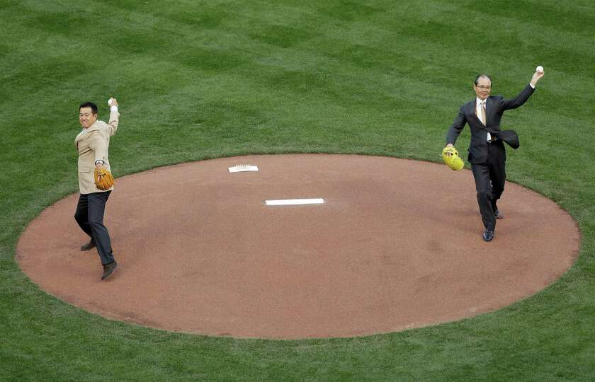 Former baseball players Tatsunori Hara, left, and Sadaharu Oh throw out the ceremonial first pitch b