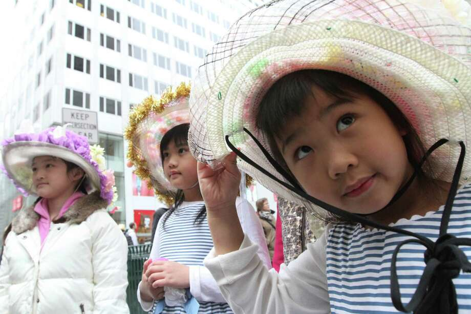 Dressed for the occasion, Elin Chau, 5, right, her sister, Elicia Chau, 7, center, and Jennifer Qiu, 9, all from the Queens borough of New York, pose for photographs on New York's Fifth Avenue as they take part in the Easter Parade, Sunday, March 31, 2013. Photo: Tina Fineberg, AP / FR73987 AP