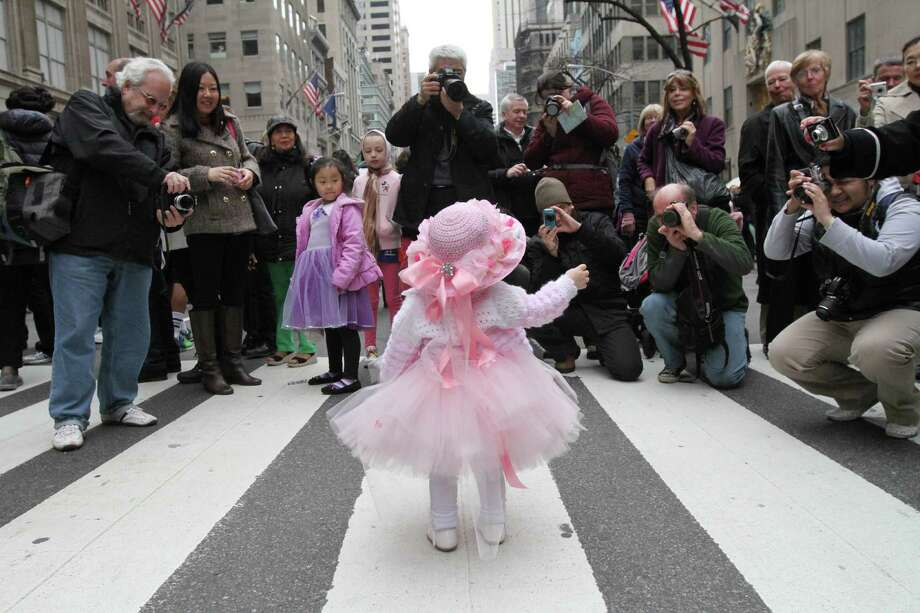 Eighteen-month-old Ariana Simmons, of New York, center, poses for photographs on New York's Fifth Avenue as she takes part in the Easter Parade Sunday March 31, 2013. Photo: Tina Fineberg, AP / FR73987 AP