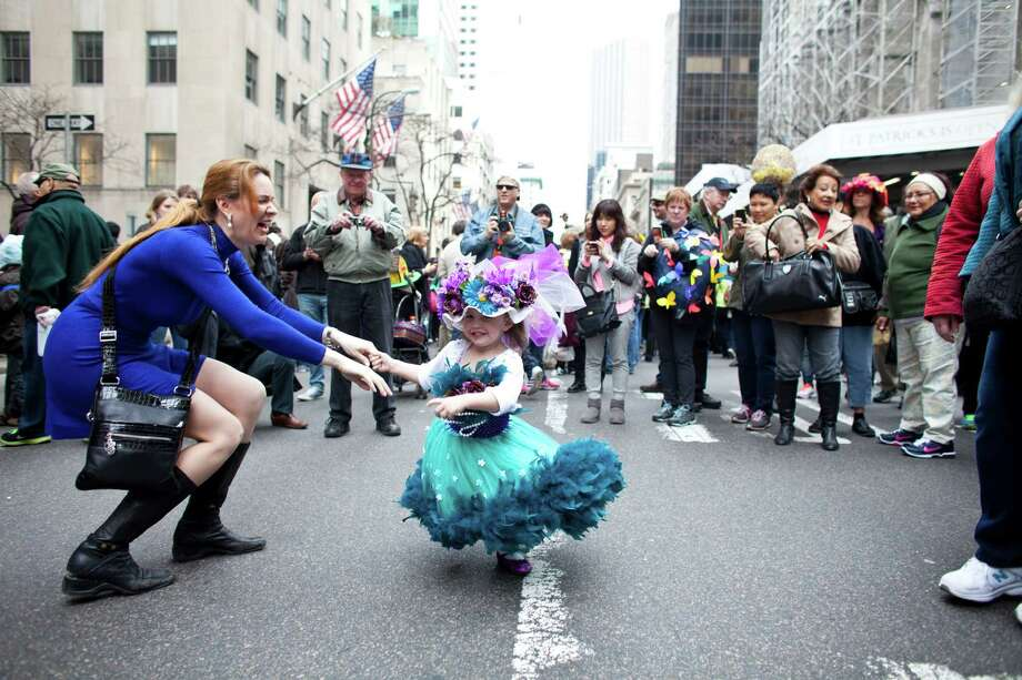 NEW YORK, NY - MARCH 31: Janice Miller plays with her 2 year old daughter, Angelina, during the annual Easter Day procession on 5th Avenue March 31, 2013 in New York City. The annual festivities attracts hundreds of New Yorkers gathering in front of St. Patrick's Cathedral wearing colorful hats and costumes celebrating one of the holiest days in the Christian calendar. Photo: Ramin Talaie, Getty Images / 2013 Getty Images