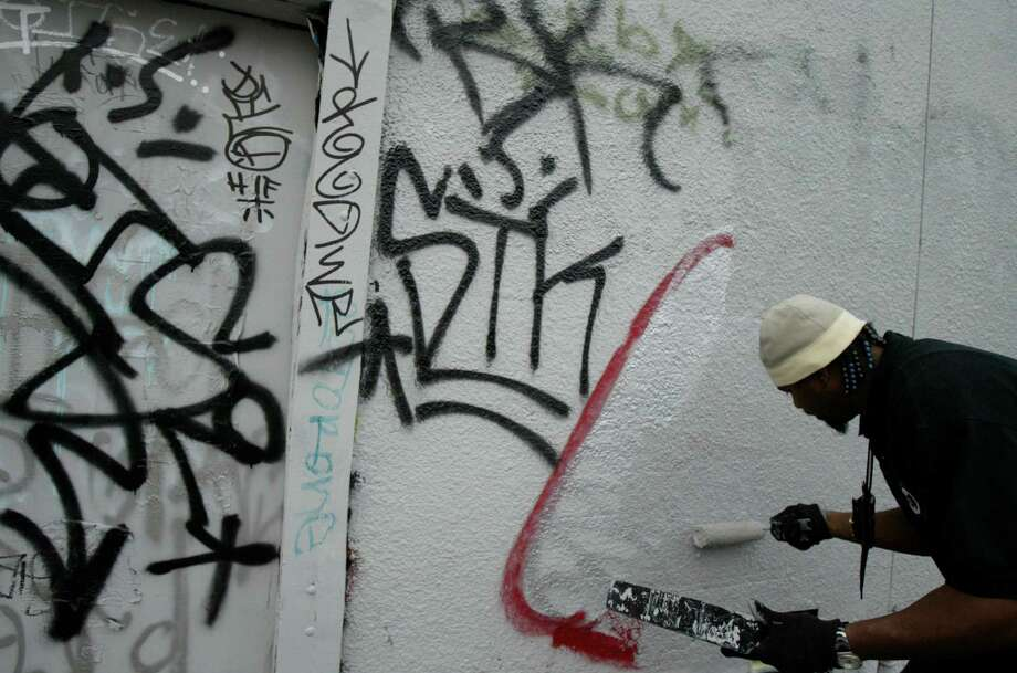 Tony Emanuel, a neighborhood protection inspector, paints over graffiti on the back of a building in Houston's Montrose area in January 2006. Criminal gangs often use graffiti to mark territory and to publicize a gang's power status. Credit: Aaron M. Sprecher Photo: For The Chronicle, Aaron M. Sprecher