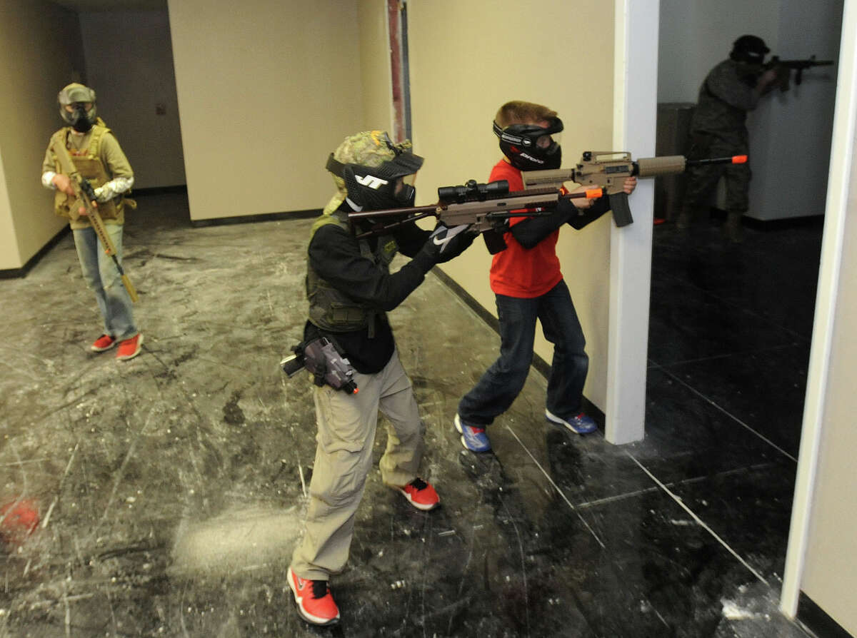 From left, Tyler Sterling, 12, Drew Bigelow, 12, Gage Morrison, 12 and Corey Glover, 18, search for the enemy during an airsoft match up at High Ground Airsoft in Beaumont on Friday. Photo taken Friday, March 30, 2013 Guiseppe Barranco/The Enterprise