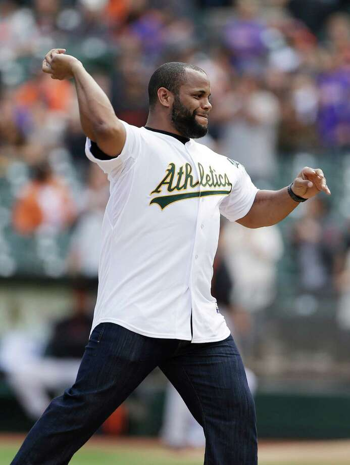 Daniel Cormier, a UFC heavyweight star throws out the first pitch before a baseball game between the San Francisco Giants and the Oakland Athletics Saturday, March 30, 2013 in Oakland, Calif.  (AP Photo/Eric Risberg) Photo: Eric Risberg, Associated Press / AP