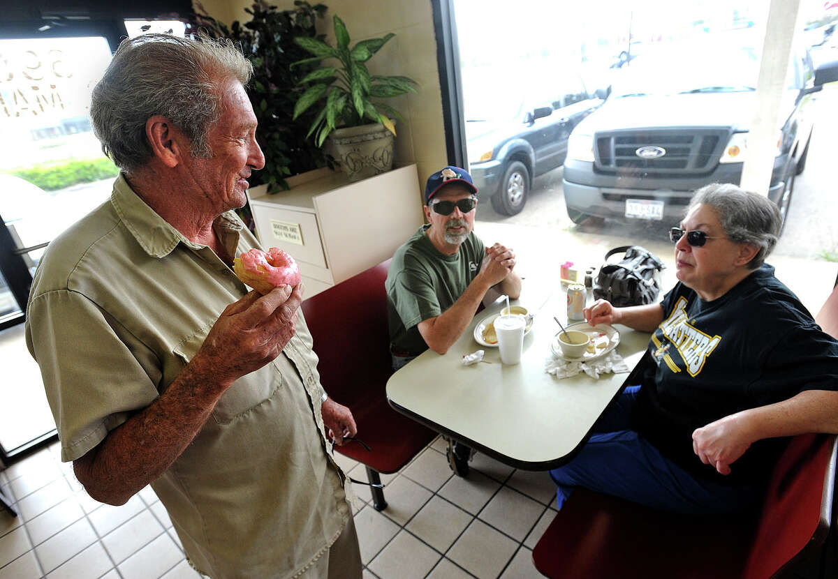 While eating a doughnut, Dale Boyett introduces himself to Lynn Harper and Mary Harper at Southern Maid Donuts in Lumberton on Friday. The trio met through a worker at the restaurant and talked about hunting at the Big Thicket. Photo taken Friday, March 28, 2013 Guiseppe Barranco/The Enterprise