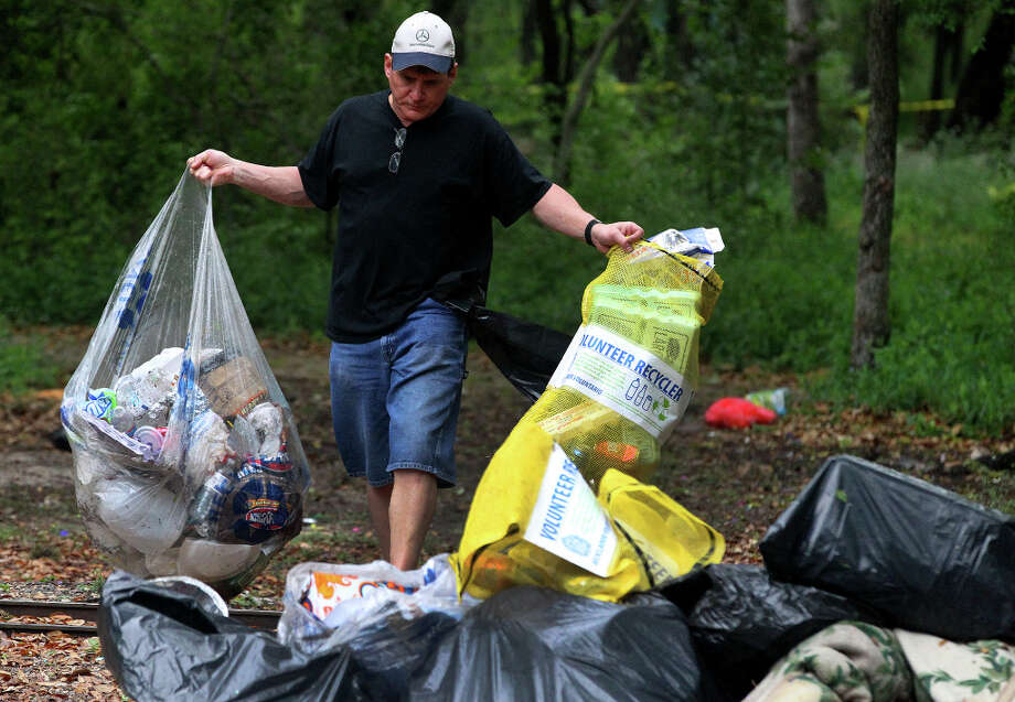 Volunteer Steve Byrd cleans up trash left at Brackenridge Park over the Easter weekend. Byrd lives near the park and said he just wanted to help out and make the park look a little bit better. Photo: JOHN DAVENPORT, SAN ANTONIO EXPRESS-NEWS / ©San Antonio Express-News/Photo may be sold to the public
