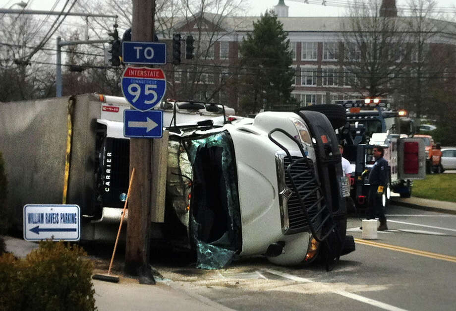 A driver escaped serious injury when his box truck loaded with milk and milk products overturned on Field Point Road in Greenwich, Conn., around 7:15 a.m. Monday, April 1, 2013. A passenger declined medical assistance. Photo: Frank MacEachern / Greenwich Time