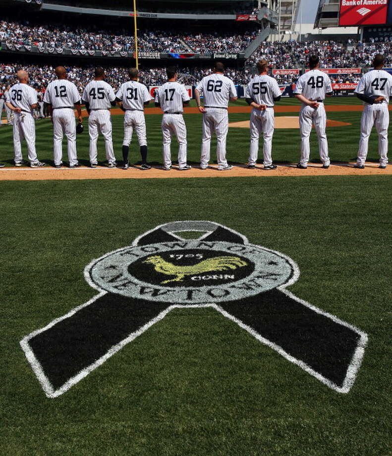 NEW YORK, NY - APRIL 01:  A marker for Newtown, Connecticut sits on a the filed during a moment of silence before the game between the New York Yankees and the Boston Red Sox during Opening Day on April 1, 2013 at Yankee Stadium in the Bronx borough of New York City.  (Photo by Elsa/Getty Images) Photo: Elsa, Getty Images / Getty Images