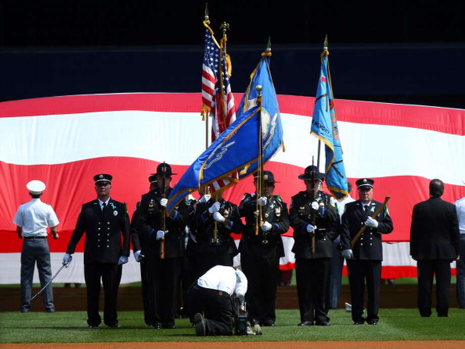 NEW YORK, NY - APRIL 01:  Members of the Newtown, Connecticut first responders serve as the color guard as the national anthem is played before the game between the New York Yankees and the Boston Red Sox before Opening Day on April 1, 2013 at Yankee Stadium in the Bronx borough of New York City.  (Photo by Elsa/Getty Images) Photo: Elsa, Getty Images / Getty Images