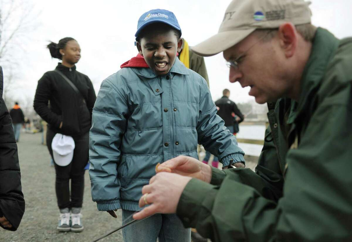 Mekkhi Keene, 9, a Brighter Choice Elementary School student, watches for the first time as Department of Environmental Conservation fish biologist Greg Kozlowski puts a worm on a hook at Six Mile Waterworks on Monday, April 1, 2013 in Albany, NY. DEC staff stocked the lake with nearly 2,000 rainbow trout on Monday. DEC staff also gave lessons on casting and about fishing in general. (Paul Buckowski / Times Union)