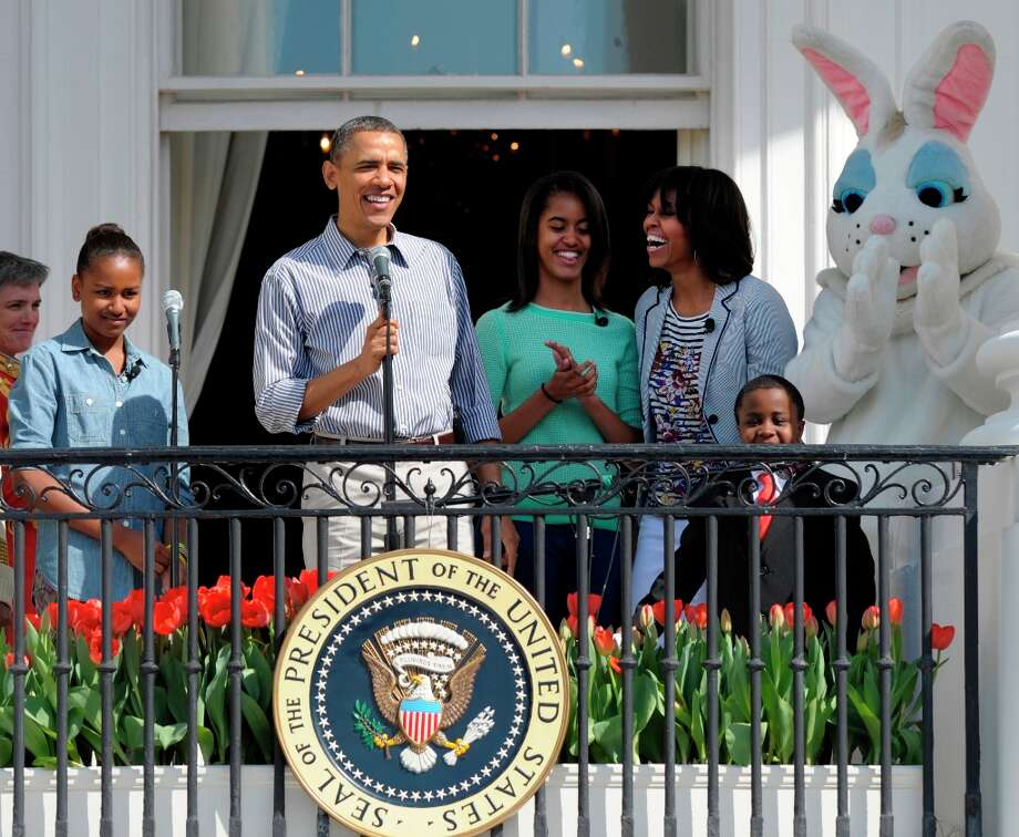President Barack Obama, accompanied by first lady Michelle Obama, daughters Sasha and Malia, The Easter Bunny and Robby Novak, better known as Kid President, speaks to the crowd on the South Lawn from the Truman Balcony of the White House in Washington, Monday, April 1, 2013, during the annual Easter Egg Roll. (AP Photo/Susan Walsh) Photo: Susan Walsh, Associated Press / AP