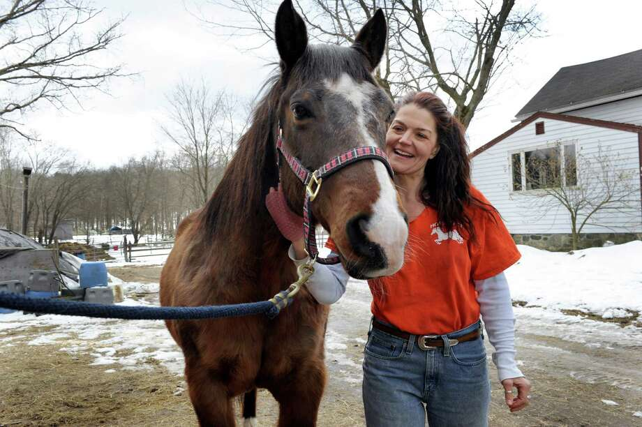 Debbie Danowski, 47, of Winsted, Conn., works with Beau, a registered quarter horse, at H.O.R.S.E. of Connecticut, in Washington, Conn., Friday, March 22, 2013. Danowski battled food addiction years ago and has written books about her experience. Photo: Carol Kaliff / The News-Times