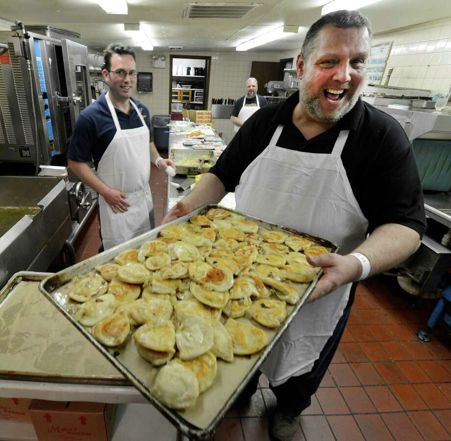 Gary Rafalik, right,  carries a tray of pierogi out to waiting customers during the Dyngus Day celebration April 1, 2013,  at the Elks lodge in Rotterdam, N.Y.   (Skip Dickstein/Times Union) Photo: SKIP DICKSTEIN / 10021460A