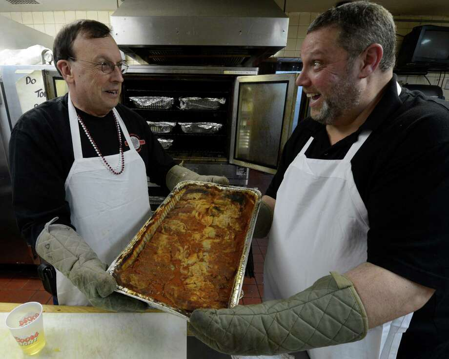 John Gosch, left, and Gary Rafalik take a tray of golumbki out of the oven for serving during the Dyngus Day celebration April 1, 2013,  at the Elks lodge in Rotterdam, N.Y.   (Skip Dickstein/Times Union) Photo: SKIP DICKSTEIN / 10021460A