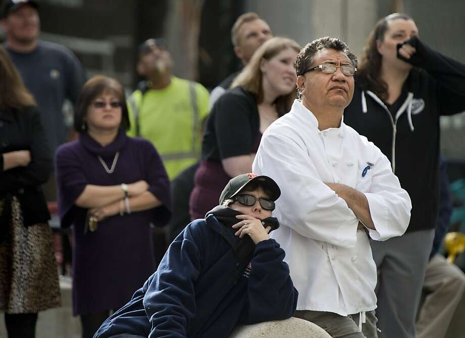 People gather near 13th and J streets to watch firefighters as they recover the body a man hanging from a rope tied to a balcony.   Fire officials said the man's death appears accidental.  Photo: Randy Pench, Associated Press