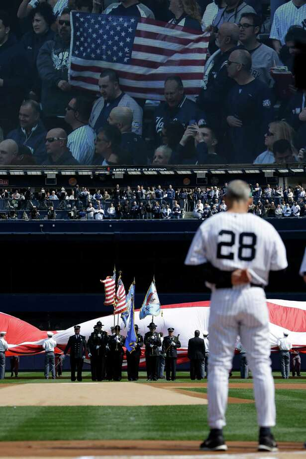 New York Yankees manager Joe Girardi (28) stands at attention as an honor guard performs a tribute to the victims of the Newtown, Ct., school shootings before an Opening Day baseball game at Yankee Stadium in New York, Monday, April 1, 2013. Photo: Kathy Willens, AP Photo/Kathy Willens / Associated Press