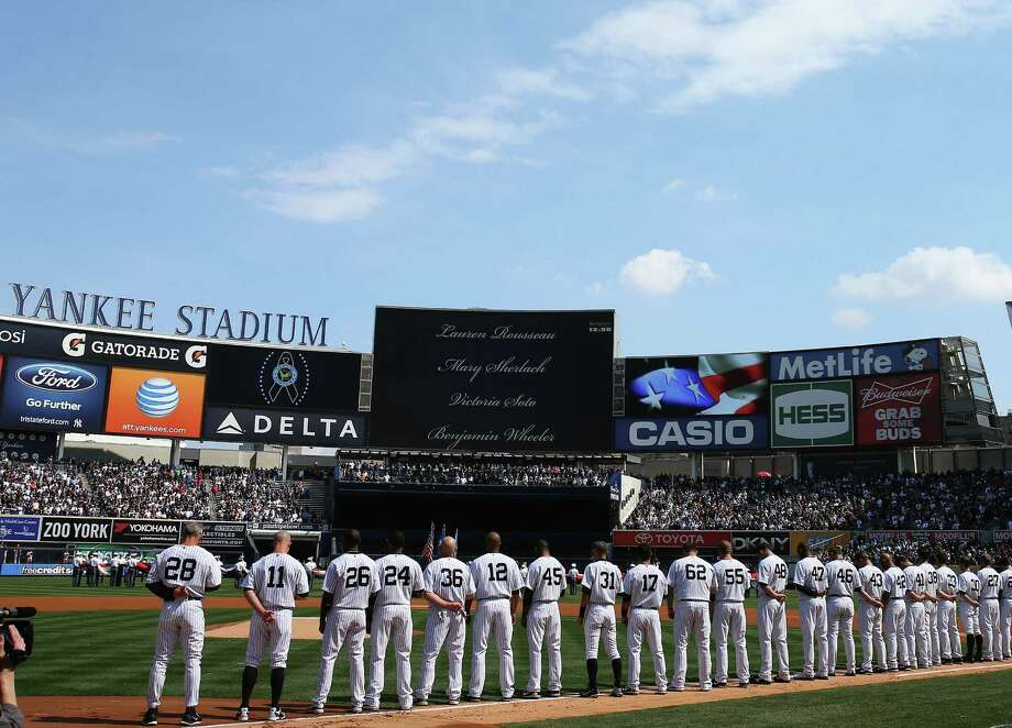 Names of the victims from the Newtown, Connecticut school shooting scroll accross the screen during a moment of silence before the game between the New York Yankees and the Boston Red Sox during Opening Day on April 1, 2013 at Yankee Stadium in the Bronx borough of New York City. Photo: Elsa, Photo By Elsa/Getty Images / 2013 Getty Images