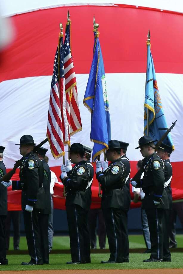 Members of the Newtown, Connecticut first responders serve as the color guard as the national anthem is played before the game between the New York Yankees and the Boston Red Sox before Opening Day on April 1, 2013 at Yankee Stadium in the Bronx borough of New York City. Photo: Elsa, Photo By Elsa/Getty Images / 2013 Getty Images