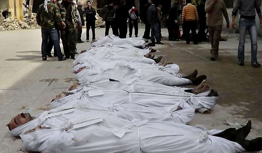 FILE - This file citizen journalism image taken on, Sunday, March. 10, 2013 and provided by Aleppo Media Center AMC which has been authenticated based on its contents and other AP reporting, shows Syrians standing next to dead bodies that have been pulled from the river near Aleppo's Bustan al-Qasr neighborhood, Syria. More than 6,000 people were killed in the Syrian civil war in March alone, according to a leading activist group that reported it was the deadliest month yet in the 2-year-old conflict. (AP Photo/Aleppo Media Center AMC, File) Photo: Hoep, Associated Press