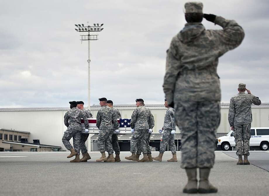Army soldiers carry the remains of Sgt. Michael Cable to a transfer vehicle at Dover Air Force Base, Del., Thursday. The U.S. death toll in Afghanistan rose sharply last month. Photo: Cliff Owen, Associated Press