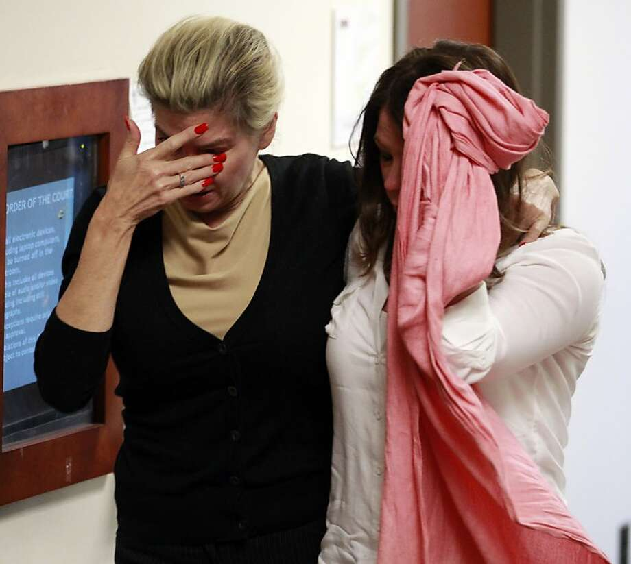 Two unidentified women hide their faces as they leave the courtroom  in the case of  Aurora theater shooting suspect James Holmes in Centennial, Colo., on Monday, April 1, 2013, after hearing that the prosecution will seek the death penalty in the case against Holmes.  Photo: Brennan Linsley, Associated Press