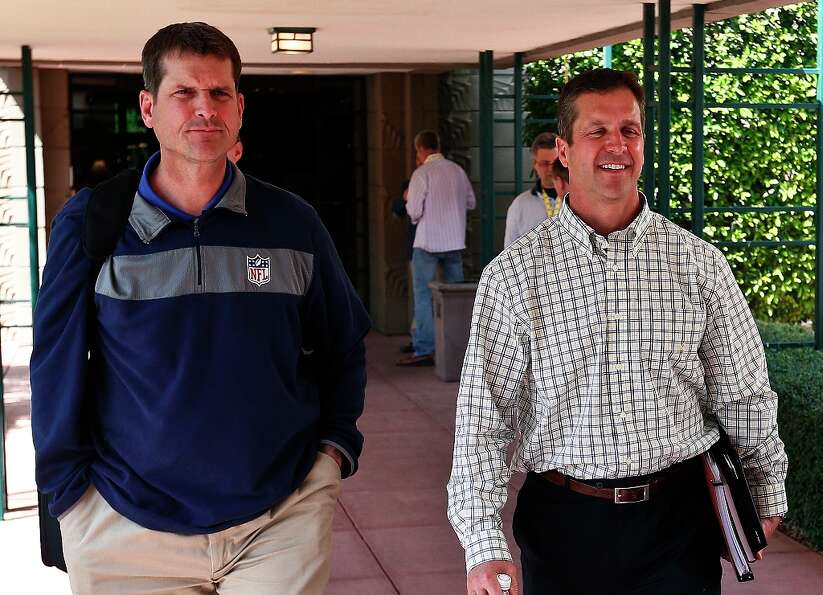 San Francisco 49ers coach Jim Harbaugh, left, walks with his brother John Harbaugh, coach of the Bal