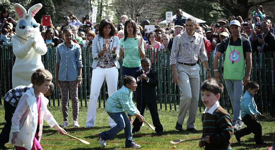 WASHINGTON, DC - APRIL 01:  U.S. President Barack Obama (2nd R), first lady Michelle Obama (3rd L), daughters Sasha (2nd L) and Malia (4th R), and Robby Novak (3rd R), who also known as the Kid President, watch as children participate during the annual White House Easter Egg Roll on the South Lawn of the White House April 1, 2013 in Washington, DC.  President Obama and first lady Michelle Obama hosted thousands of people during the annual celebration of Easter. Photo: Alex Wong, Getty Images / 2013 Getty Images