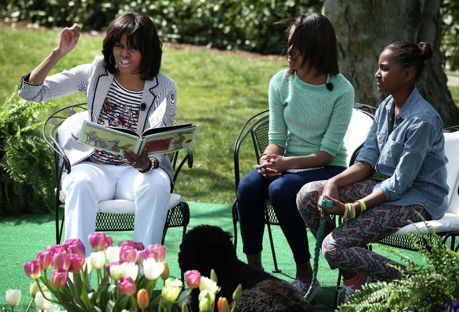 WASHINGTON, DC - APRIL 01:  (AFP OUT)  U.S. first lady Michelle Obama (L) reads the story Cloudy with a Chance of Meatballs to children as daughters Sasha (R) and Malia (2nd L) look on during the annual White House Easter Egg Roll on the South Lawn of the White House April 1, 2013 in Washington, DC.  President Barack Obama and first lady Michelle Obama hosted thousands of people during the annual celebration of Easter. Photo: Alex Wong, Getty Images / 2013 Getty Images