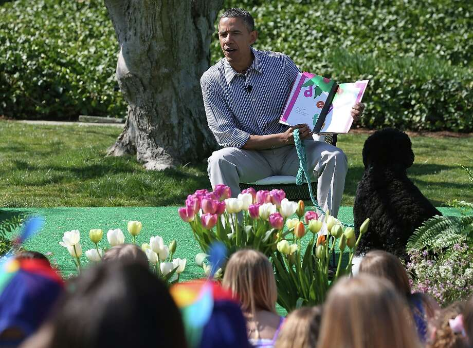 U.S. President Barack Obama sits with his dog Bo and reads a book to children during the annual Easter Egg Roll on the White House tennis court April 1, 2013 in Washington, D.C. Thousands of people are expected to attend the 134-year-old tradition of rolling colored eggs down the White House lawn that was started by President Rutherford B. Hayes in 1878.  (Pool photo by Mark Wilson/Getty Images via Abaca Press/MCT) Photo: Mark Wilson/Getty Images, McClatchy-Tribune News Service / Abaca Press
