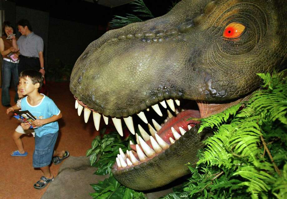 Children run away from a dinosaur in a promotion in a Tokyo department store for the 'Jurassic Park' ride at Universal Studios Japan on August 11, 2004. Photo: YOSHIKAZU TSUNO, AFP/Getty Images / 2004 AFP