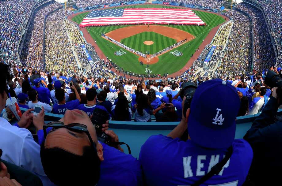 Fans listen to the national anthem during the Los Angeles Dodgers' opening day baseball game against the San Francisco Giants at Dodger Stadium, Monday, April 1, 2013, in Los Angeles. Photo: Mark J. Terrill, Associated Press / AP