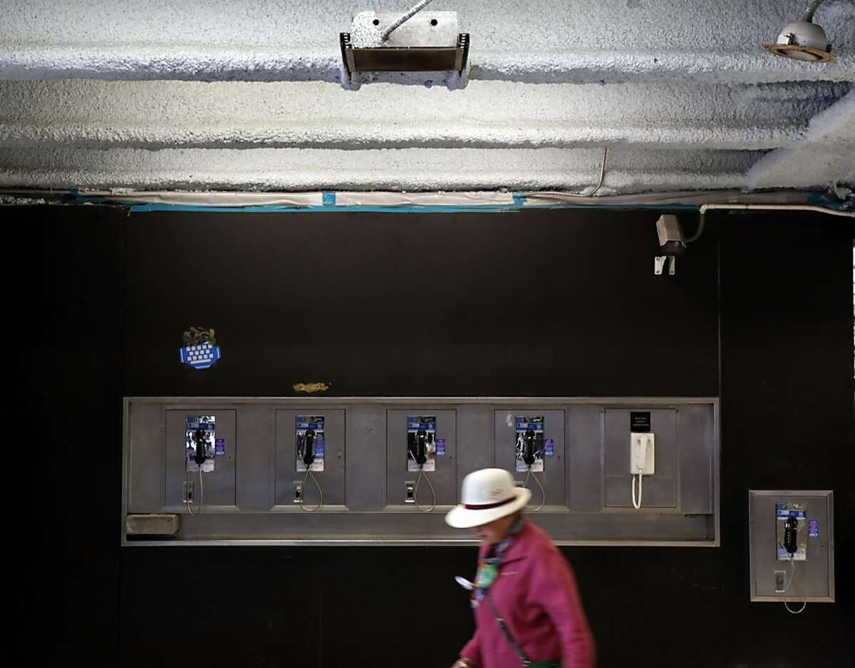 A commuter walks past pay phones at BART's Powell Street Station. Although old-school phone booths are mostly gone, about 200 coin-operated phones still exist in San Francisco.