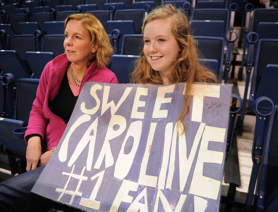 Sitting with her mother Ruth, left, Emma Robin, of Longmeadow, MA, holds a sign for her favorite player, UCONN's Caroline Doty, before the start of UCONN's elite eight matchup with Kentucky at the Webster Bank Arena in Bridgeport, Conn. on Monday, April 1, 2013. Photo: Brian A. Pounds / Connecticut Post
