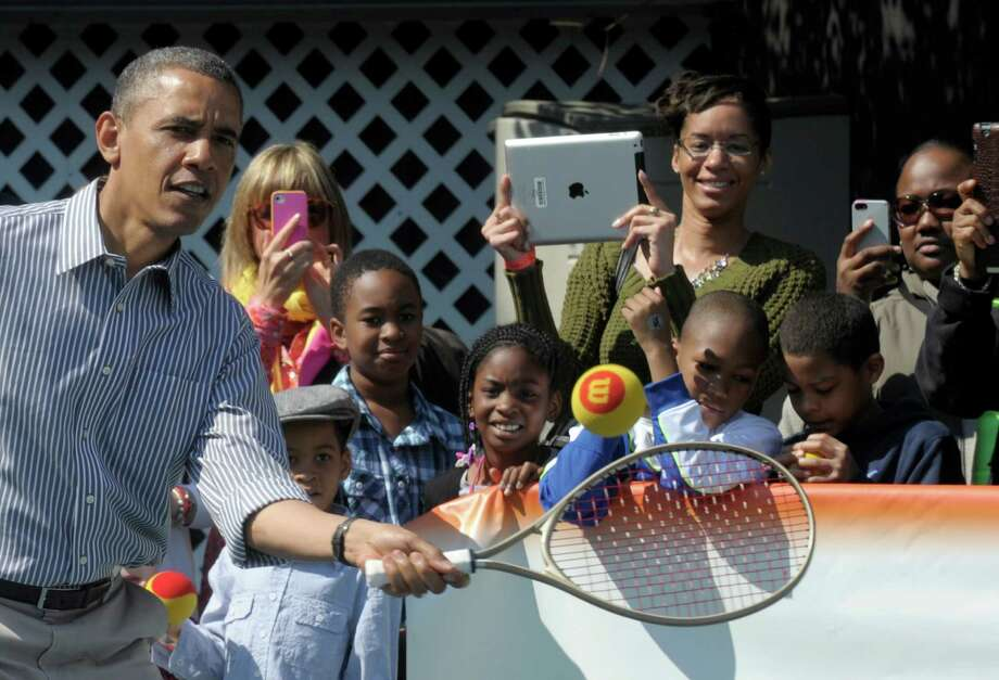 President Barack Obama eyes the ball during a tennis game at the annual Easter Egg Roll on the South Lawn of the White House in Washington, Monday, April 1, 2013. (AP Photo/Susan Walsh) Photo: Susan Walsh