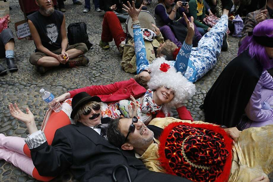 Ty McKenzie (derby) and Jacob Zafir (front right) lie on Teri Angst (white hair), all from San Francisco, in a plaza on Sansome at Sutter streets as they rest during the 35th annual St. Stupid's Day parade in San Francisco, California, on Monday, April 1, 2013. Photo: Liz Hafalia, The Chronicle