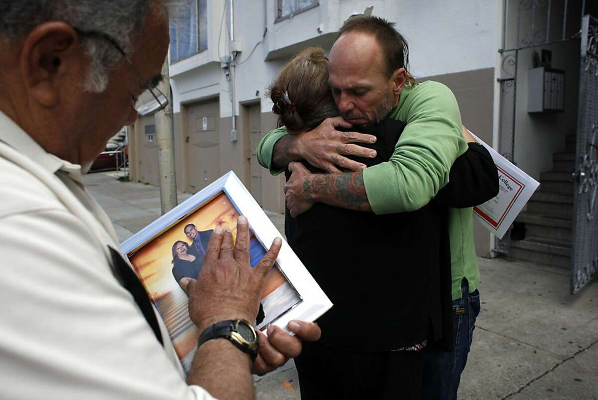 Carlos Valdiviezo holds a photo of his wife Margarita and son, as neighbor Lucky Fisher comforts her.
