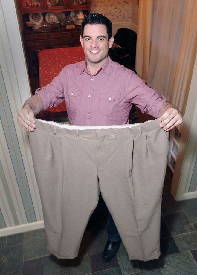 Anthony Accinno, 32, holds a pair of his pants that he wore before he underwent bariatric surgery, at his New Canaan home, Friday night, March 22, 2013. Last January Accinno had a gastric sleeve procedure to reduce the size of his stomach, and has lost more than 100 pounds. Photo: Bob Luckey / Greenwich Time
