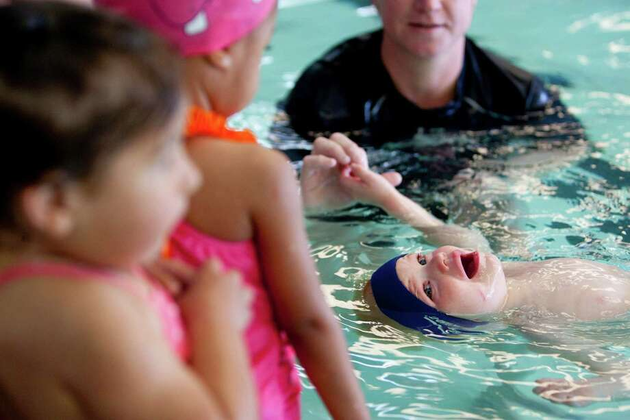 Swim instructor Andrea Smith works with 2-year-old Ben Schafer, at the Houston Swim Club in Sharpstown after a press conference for April Pools Day about pool safety Monday, April 1, 2013, in Houston.  April Pools Day focuses on water safety education and drowning  prevention for parents and children.  Last year 24 in the greater Houston area and 74 children in Texas died from drowning.  This year already two children have drown in the greater Houston area. For more information visit the Texas Drowning Prevention Alliance at: txdpa.org or Safe Kids Greater Houston at www.safekidsgreaterhouston.org Photo: Johnny Hanson, Houston Chronicle / © 2013  Houston Chronicle