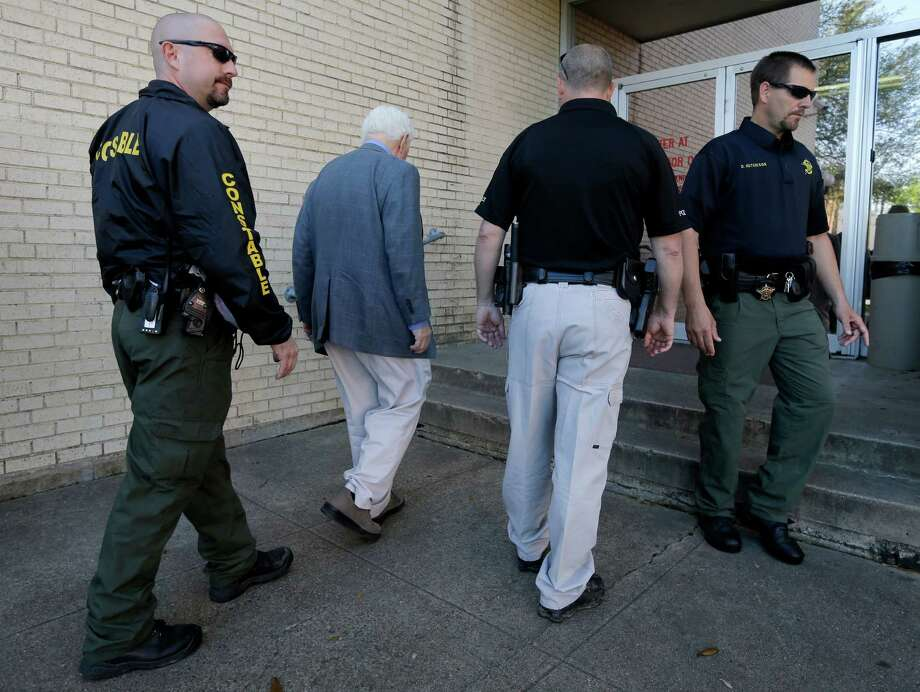 Kaufman County lawmen escort an employee inside the courthouse Monday as police throughout Texas were on high alert. Photo: Tony Gutierrez, STF / AP