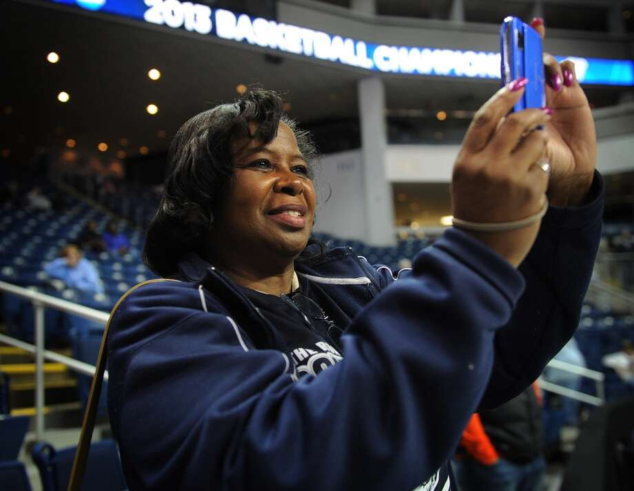 Self described huge fan Deborah Benn of Norwalk snaps photos during warmups before UCONN's elite eight women's basketball matchup with Kentucky at the Webster Bank Arena in Bridgeport, Conn. on Monday, April 1, 2013.