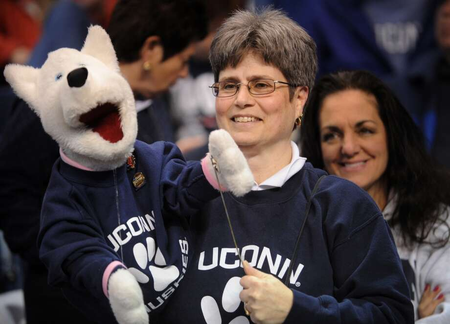 Carol McKenzie of Simsbury and her husky puppet J.J. attend the UCONN women's basketball matchup with Kentucky in the elite eight round of the NCAA Women's Basketball Tournament at the Webster Bank Arena in Bridgeport, Conn. on Monday, April 1, 2013.