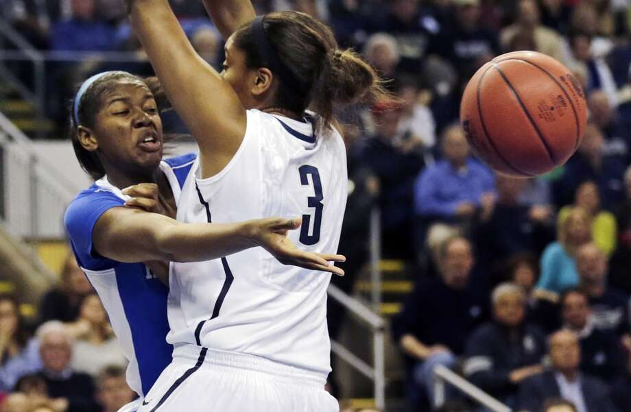 Kentucky center DeNesha Stallworth, left, dumps off the ball as she is pressured by Connecticut forward Morgan Tuck (3) in the first half of a women's NCAA regional final basketball game in Bridgeport, Conn., Monday, April 1, 2013. (AP Photo/Charles Krupa)