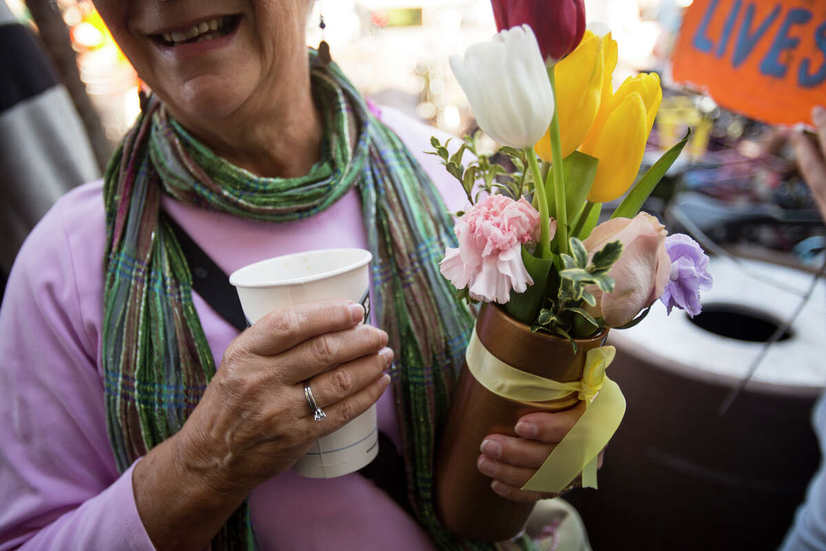In a gathering crowd, Janet Parks carries a bouquet of flowers during a memorial walk Monday in the Wedgwood neighborhood of Seattle. The timing of the march marked one week since Judy and Dennis Schulte lost their lives to a suspected drunken driver while crossing Northeast 75th Street at 33rd Avenue Northeast with their daughter-in-law, Karina Ulriksen-Schulte, and her then 10-day-old son, Elias. (Jordan Stead, seattlepi.com)
