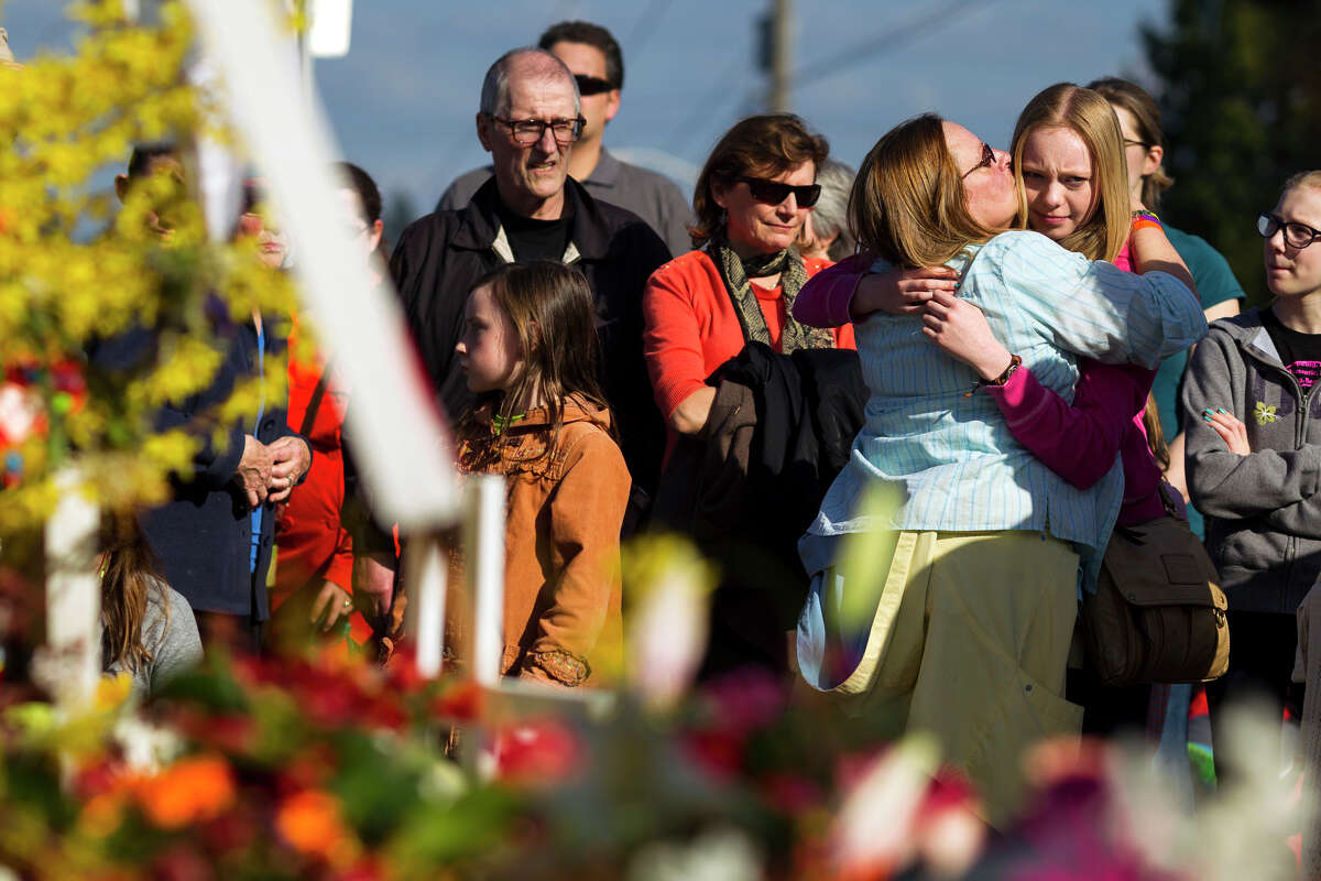 Susan Tanner, in blue, and Sierra Schulte, 15, in pink, both relatives of the late Dennis Schulte, embrace during a memorial walk Monday in the Wedgwood neighborhood of Seattle. The timing of the march marked one week since Judy and Dennis Schulte lost their lives to a suspected drunken driver while crossing Northeast 75th Street at 33rd Avenue Northeast with their daughter-in-law, Karina Ulriksen-Schulte, and her then 10-day-old son, Elias. (Jordan Stead, seattlepi.com)