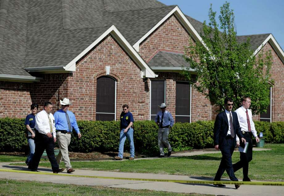 Law enforcement officials walk out of the home of Kaufman District Attorney Mike McLelland Monday, April 1, 2013, near Forney, Texas. McLelland and his wife were both murdered at their home Saturday. (AP Photo/Tony Gutierrez) Photo: Tony Gutierrez