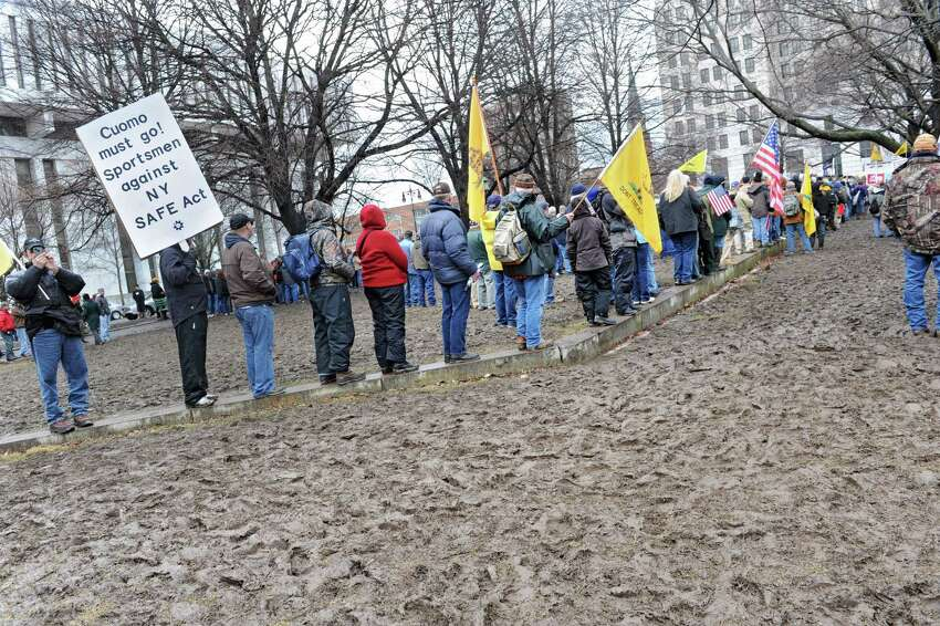 People stand on a small concrete wall to avoid standing in thick mud as the New York State Rifle & Pistol Association holds its 5th Annual Lobby Day and Rally at Capitol Park on Wednesday Feb. 27, 2013 in Albany, N.Y. (Lori Van Buren / Times Union)