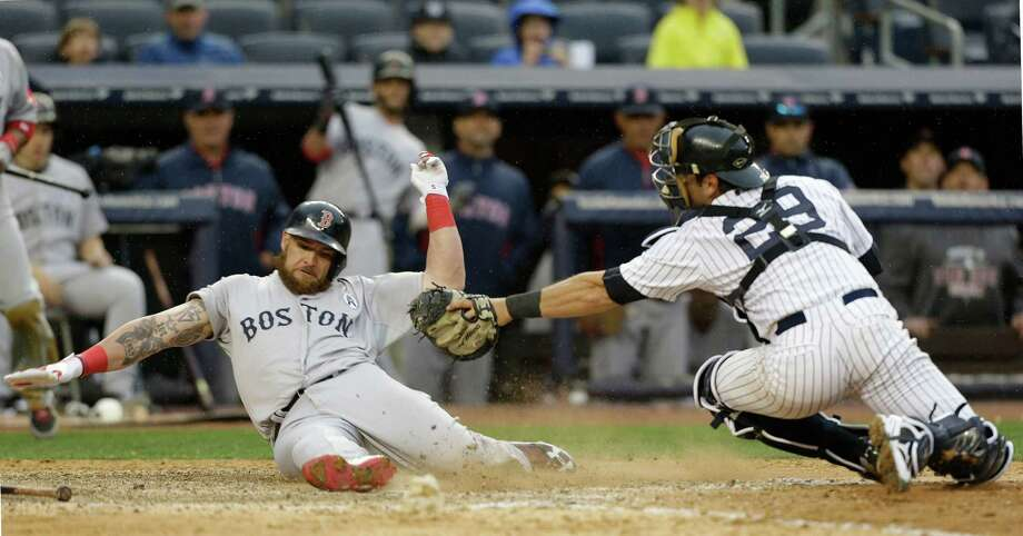 Boston Red Sox Jonny Gomes, left, scores on  a ninth-inning error by New York Yankees second baseman Robinson Cano (not shown) in an opening day baseball game  at Yankee Stadium in New York, Monday, April 1, 2013.  (AP Photo/Kathy Willens) Photo: Kathy Willens